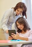Little girl with teacher and tablet pc at school Stock Images