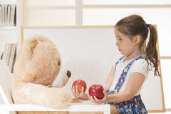 Little girl teaching her toy bear friend to count with apples, indoor shot. Little lovely caucasian child sharing apples with her Teddy bear friend. Cute toddler Royalty Free Stock Images