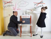 Little girl teaching mathematics to an adult dunce Royalty Free Stock Image