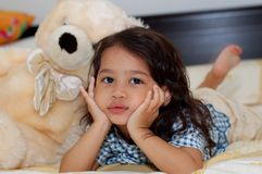Little Girl and Teddy Bear. A little girl lying on the bed with teddy bear at her side Royalty Free Stock Photos