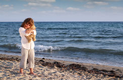 Little girl with teddy bear on beach Royalty Free Stock Photos