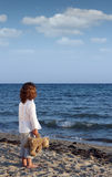 Little girl with teddy bear on beach Stock Photography