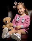 Little girl with a teddy bear on a black background. royalty free stock photos