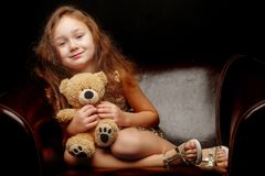 Little girl with a teddy bear on a black background. A nice little girl with a teddy bear. Studio photo on a black background. The concept of a happy childhood royalty free stock photography