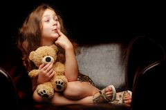 Little girl with a teddy bear on a black background. A nice little girl with a teddy bear. Studio photo on a black background. The concept of a happy childhood stock photography