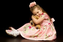 Little girl with a teddy bear on a black background. A nice little girl with a teddy bear. Studio photo on a black background. The concept of a happy childhood stock photos