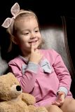 Little girl with a teddy bear on a black background. A nice little girl with a teddy bear. Studio photo on a black background. The concept of a happy childhood royalty free stock image