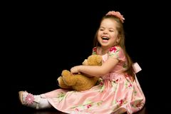 Little girl with a teddy bear on a black background. A nice little girl with a teddy bear. Studio photo on a black background. The concept of a happy childhood stock images