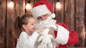 Little girl with teddy bear checking Santa`s beard. Professional shot on BMCC RAW with high dynamic range. You can use it e.g. in your commercial video Royalty Free Stock Photos