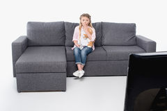 Little girl with teddy bear feeling scared while watching tv Stock Image