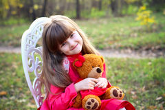 Little girl with a teddy bear in forest Stock Photos