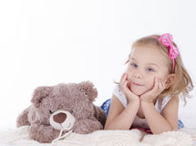 Little girl and teddy bear lying Stock Photography