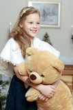 Little girl with a Teddy bear near the fireplace. stock images