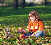 Little girl and teddy bear in park Stock Photos