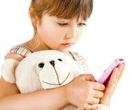 Little girl teddy bear phone. Sweet little girl cuddling teddy bear holding pink mobile phone, isolated on white Royalty Free Stock Photo