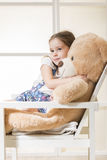 Little girl with with teddy bear. Portrait of expressive little girl hugging huge plush bear, indoor shot on white room Royalty Free Stock Images