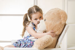 Little girl with with teddy bear. Portrait of expressive little girl hugging and kissing huge plush bear, indoor shot on white room Royalty Free Stock Images