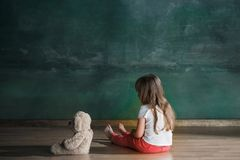 Little girl with teddy bear sitting on floor in empty room. Autism concept. Little autistic girl with teddy bear sitting on floor at empty room. Autism concept Royalty Free Stock Photo