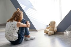 Little girl with teddy bear sitting on floor near window. In empty room. Autism concept Royalty Free Stock Photography