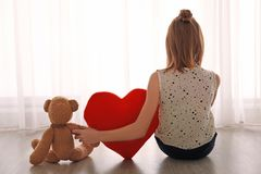 Little girl with teddy bear sitting on floor near window Royalty Free Stock Photos