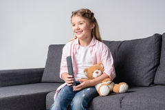 Little girl with teddy bear sitting on sofa and watching tv Stock Photos