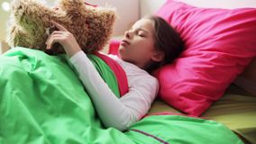 Little girl with teddy bear sleeping at home stock video
