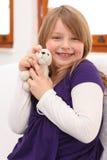 Little girl with teddy bear on sofa Stock Photos