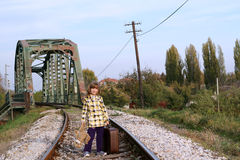 Little girl with teddy bear standing on railroad. Little girl with suitcase and teddy bear standing on railroad royalty free stock image