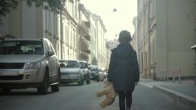 Little girl with a teddy bear is walking down the street alone. stock footage