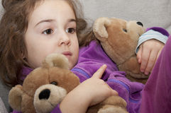 Little girl with teddy bears. Thoughtful girl that fades two teddy bears Royalty Free Stock Photo