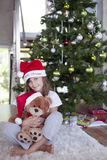 Little girl with teddy and christmas tree Stock Image