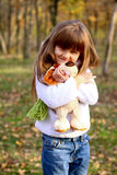 Little girl with teddy dog in autumn forest Royalty Free Stock Photography