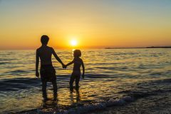 Little girl and teenager bathing on a beach at sunset stock photo
