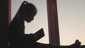 A little girl teenager imagining story with book at open window on sill on sunset background. Child reading book at home