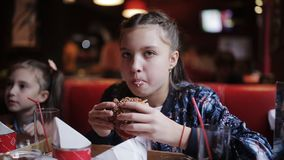 Little girl teenager with pleasure eating a burger in a cafe. hamburger and french fries in fast food stock video footage