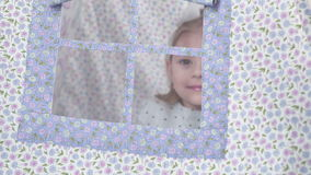 Little girl in teepee tent looks out the window stock video footage