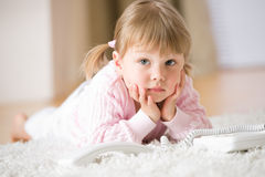 Little girl with telephone lying down on carpet Stock Photography