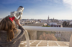 Little girl with telescope pointing to old town landmarks over M Royalty Free Stock Images