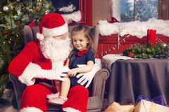 Little girl telling her Christmas wish in Santa Claus Royalty Free Stock Photo