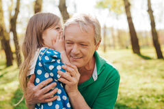 Little girl telling secret to grandpa. Adorable cute girl whispering to grandfather ear during the walk in park Royalty Free Stock Images