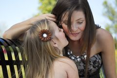 A little girl tells her mom a secret. A young little girl tells her mom a secret on a park bench Royalty Free Stock Photography