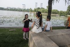 A little girl tells stories to two children at Xuanwu Lake. A young girl tells stories to two children at Xuanwu Lake in Gulou District, Nanjing, Xuanwu Lake Royalty Free Stock Photos