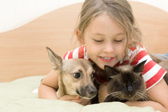 Little girl tenderly embraces pets. Little girl tenderly embraces a dog and a cat Royalty Free Stock Image