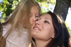 Little girl tenderly kisses mom. Little girl tenderly kisses mother sitting in a tree in park Stock Image