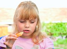 Little girl tests the sandwich with red caviar Stock Photo