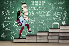 Little girl with textbooks and doodles Royalty Free Stock Photo
