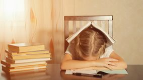 Tired schoolgirl with books at table royalty free stock photo