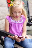 Little Girl Texting. A young little blond girl sending a text on a cell phone. Pink shirt, bow in her hair. Shallow depth of field Stock Photo