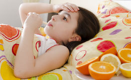 Little girl with a thermometer in bed. Sick little 7 years old with a thermometer royalty free stock photos