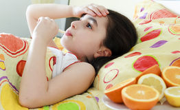 Little girl with a thermometer in bed. And fruits stock photo